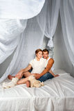 Happy Pregnant Couple dressed in white embrace each other sitting on a bed with a canopy on a white background Royalty Free Stock Photo