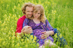 Happy pregnant couple hugging in nature Royalty Free Stock Photo