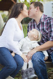 Happy Pregnant Couple Kisses as Baby Girl Watches Stock Images