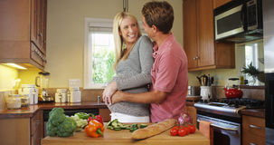 Happy pregnant couple in the kitchen Stock Image