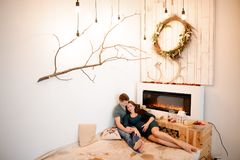 Happy pregnant couple lying near the burning fireplace Royalty Free Stock Photography
