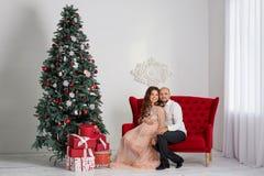 Happy pregnant couple near the Christmas tree.  Royalty Free Stock Photos