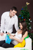 Happy pregnant couple near the christmas tree Royalty Free Stock Photo