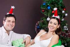 Happy pregnant couple near the christmas tree. Happy pregnant couple with presents near the christmas tree Royalty Free Stock Images