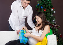 Happy pregnant couple near the christmas tree Stock Images