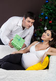 Happy pregnant couple near the christmas tree Stock Photo