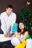 Happy pregnant couple near the christmas tree Stock Photos
