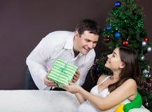 Happy pregnant couple near the christmas tree. Happy pregnant couple with presents near the christmas tree Royalty Free Stock Image