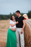 Happy pregnant couple on oat field Stock Images