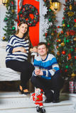 Happy pregnant couple posing near a Christmas tree. Happy pregnant couple hugging. Christmas concept happy pregnancy Royalty Free Stock Image