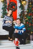 Happy pregnant couple posing near a Christmas tree Royalty Free Stock Image