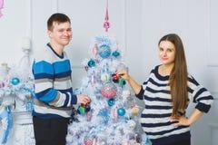 Happy pregnant couple posing near a Christmas tree Stock Photography