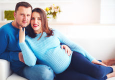 Happy pregnant couple relaxing on couch at home Stock Photo