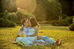 Happy pregnant couple sitting on the grass in park royalty free stock photos