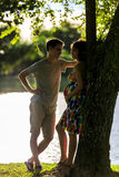 Happy pregnant couple standing at ttopical park in back light Stock Photography
