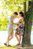 Happy pregnant couple standing at ttopical park in back light Stock Photos