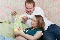 Happy pregnant family with children's clothes. Royalty Free Stock Photography