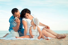 Happy pregnant family with a daughter on the beach. Stock Image