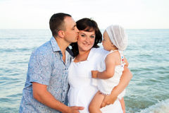 Happy pregnant family with a daughter on the beach. Stock Photos