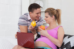 Happy pregnant family with fruit. Royalty Free Stock Photography