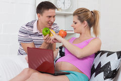 Happy pregnant family with fruit. Stock Image