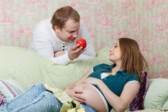 Happy pregnant family with fruit. Royalty Free Stock Images