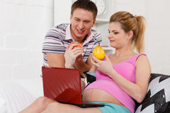 Happy pregnant family with fruit. Stock Photo