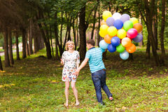 Happy pregnant family having fun during the walk in summer nature. Royalty Free Stock Image