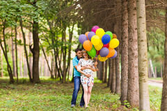 Happy pregnant family having fun during the walk in summer nature. Royalty Free Stock Images