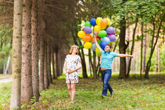 Happy pregnant family having fun during the walk in summer nature. Royalty Free Stock Photography
