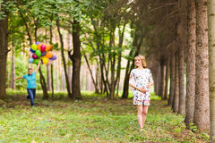 Happy pregnant family having fun during the walk in summer nature. Royalty Free Stock Photos