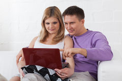 Happy pregnant family with laptop. Stock Image