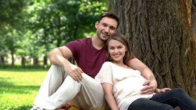 Happy pregnant family sitting under tree in park, courses for future parents royalty free stock image