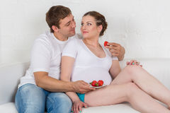 Happy pregnant family with strawberries. Stock Image