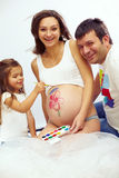 Happy pregnant family of three drawing belly. Beautiful happy pregnant family of three are drawing mom's belly Royalty Free Stock Image