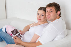 Happy pregnant family with ultrasound picture Royalty Free Stock Photography
