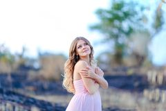 Happy pregnant female person wearing pink dress standing in blurred background. Concept of beauty and pregnance photo session Royalty Free Stock Photos