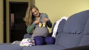Happy pregnant future mom prepare newborn clothes and shoes stock video