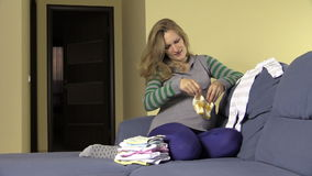 Happy pregnant future mother prepare newborn clothes and shoes stock video footage