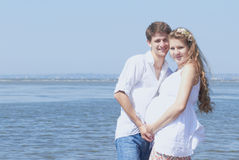 Happy pregnant girl and her loving husband. Young family waiting for their first child to be born soon Stock Photos