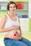 Happy pregnant girl with palm stamps on belly Royalty Free Stock Photos