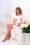 Happy pregnant girl in a white lace dress sitting on a bed near roses Royalty Free Stock Photo
