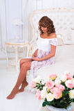 Happy pregnant girl in a white lace dress sitting on a bed near roses Royalty Free Stock Photos
