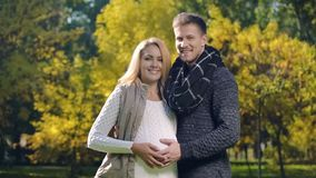 Happy pregnant lady and husband stroking belly and looking at camera, parents stock image