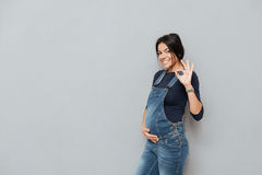 Happy pregnant lady make okay gesture. Image of happy pregnant lady standing over grey background and make okay gesture. Looking at camera Stock Photography