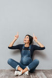Happy pregnant lady sitting on floor pointing to copyspace. Image of happy pregnant lady sitting on floor over grey background pointing to copyspace. Looking Royalty Free Stock Photos
