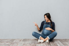 Happy pregnant lady sitting on floor pointing to copyspace. Image of happy pregnant lady sitting on floor over grey background pointing to copyspace. Looking at Stock Images