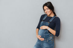 Happy pregnant lady standing over grey background. royalty free stock images