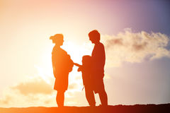Happy pregnant mother and father with son at sunset Stock Image