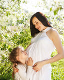 Happy pregnant mother and her little daughter. In the spring day Royalty Free Stock Photo